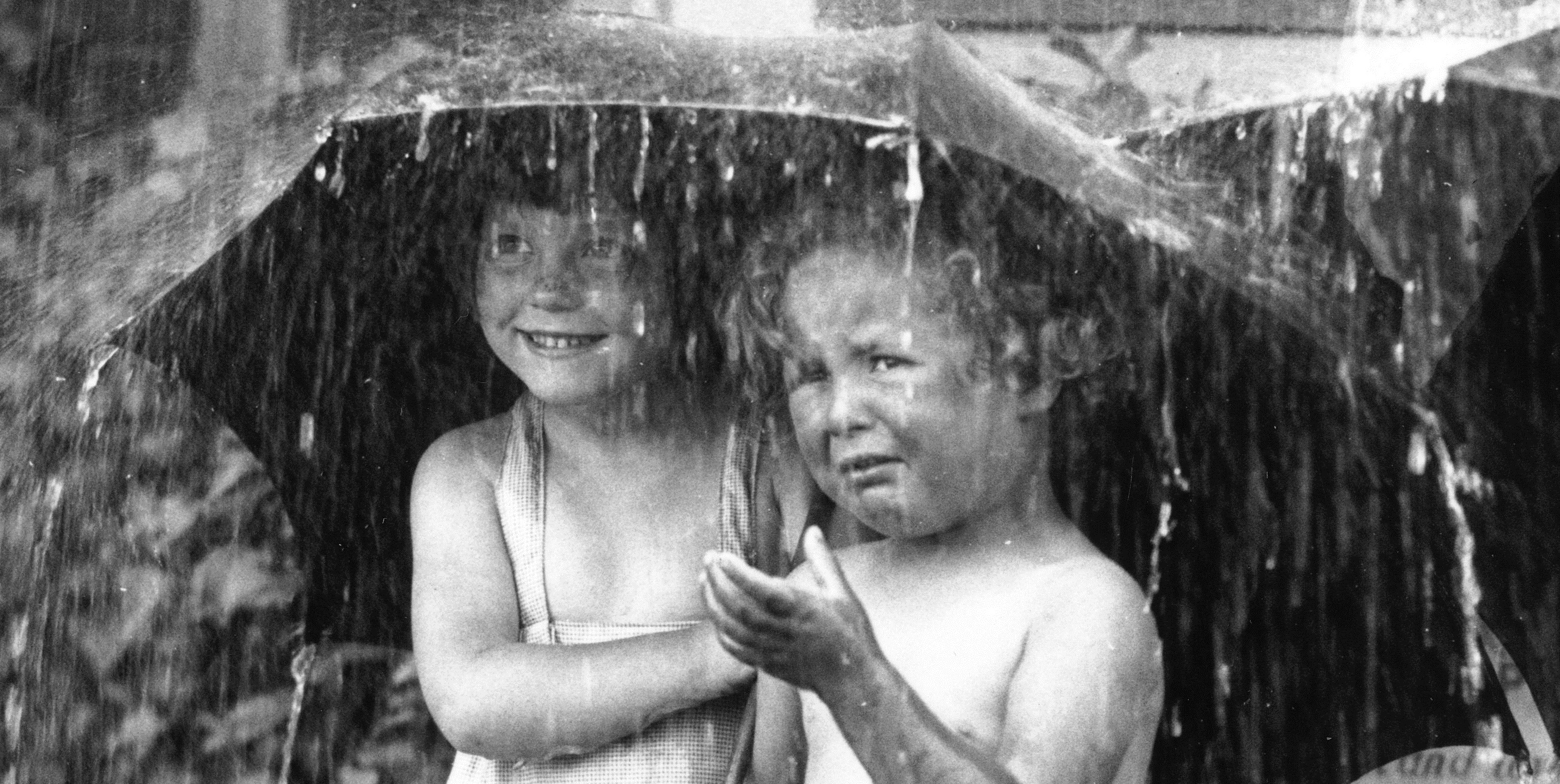 21st June 1934: Two young children at Dr Barnardo's sheltering under an umbrella from a garden shower. (Photo by Fox Photos/Getty Images)